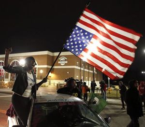Gina Gowdy joins protesters on the street outside a Ferguson, Mo., fire station, Wednesday, March 4, 2015, in Ferguson. (AP Image)