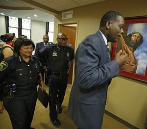 In this photo taken on Aug. 18, 2014, Dallas County District Attorney, Craig Watkins. right, with Dallas Police Chief David Brown, center, and Dallas County Sheriff Lupe Valdez walk into an open meeting at the St. Paul United Methodist Church in Dallas, to address the concerns of police shootings. (AP Image)