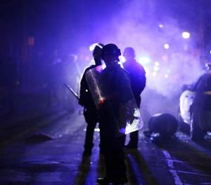 In this Nov. 25, 2014 file photo, police officers watch protesters as smoke fills the streets in Ferguson, Mo. (AP Photo/Charlie Riedel)