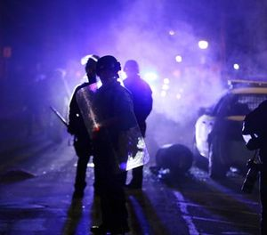 In this Nov. 25, 2014 file photo, police officers watch protesters as smoke fills the streets in Ferguson, Mo. (AP File Photo/Charlie Riedel)