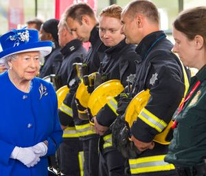 Britain's Queen Elizabeth II, left, meets firefighters and paramedics during a visit to the Westway Sports Centre which is providing temporary shelter for those who have been made homeless by the fire at Grenfell Tower. (Dominic Lipinski/Pool Photo via AP)