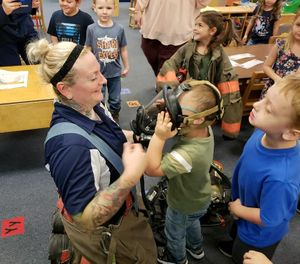 "West Virginia firefighter Wendi Wentzell-Cuc shows a child her face mask during Fire Prevention Week. She and the department signed LION's ""Not In Our House"" pledge as part of their efforts to raise awareness and help firefighters reduce their risk of exposure to carcinogens. (image/Wendi Wentzell-Cuc)"