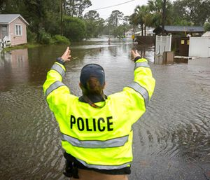 A City of Tybee police officer checks the well being of a resident fleeing her flooded home on Tybee Island, Ga. (AP Photo/Stephen B. Morton)