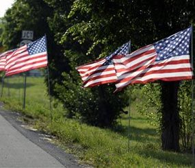 In this Thursday, May 30, 2013, photo, United States flags line the route of the funeral procession of Bardstown, Ky. Officer Jason Ellis during his funeral service. (AP Image)