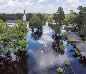 United States Coastguardsmen navigate an inflatable boat up Sherwood Drive in Conway, s.c., checking on residents. (Photo/AP)