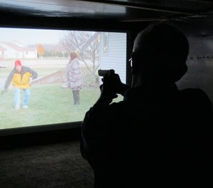 Mark Tulloch, of Kettering, Ohio, takes aim in a firearms training simulator at the Clark County Fair on Wednesday, July 26, 2017, in Springfield, Ohio. (AP Photo/Kantele Franko)