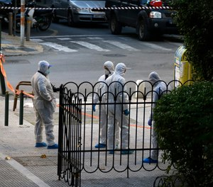 Greek forensic experts search at the scene after an explosion outside the Orthodox church of Agios Dionysios in the upscale Kolonaki area of Athens, Thursday, Dec. 27, 2018. Police in Greece say an officer has been injured in a small explosion outside a church in central Athens while responding to a call to investigate a suspicious package. (AP Photo/Thanassis Stavrakis)