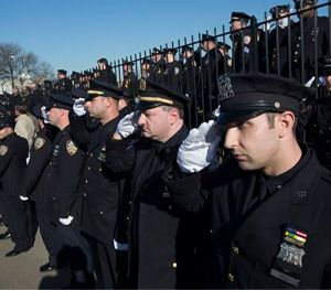 Police officers salute as the hearse of New York city police officer Rafael Ramos drives along his funeral procession route in the Glendale section of Queens. (AP Image)