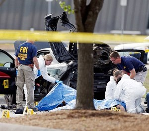 In this May 4, 2015 file photo, FBI crime scene investigators document the area around two deceased gunmen and their vehicle outside the Curtis Culwell Center in Garland, Texas. (AP Photo/Brandon Wade, File)