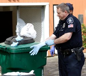 Seattle Police officer Aaron Stoltz puts on a glove as he prepares to search garbage and recycling bins, Friday, April 15, 2016, after human remains were found in a nearby container in Seattle. (AP Photo/Ted S. Warren)