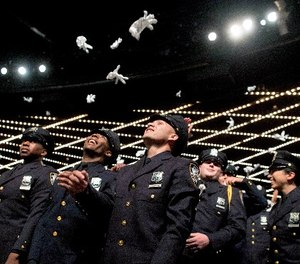 The newest members of the New York City police toss their gloves into the air during their graduation ceremony, Thursday, June 29, 2017, in New York. (AP Photo/Mary Altaffer)