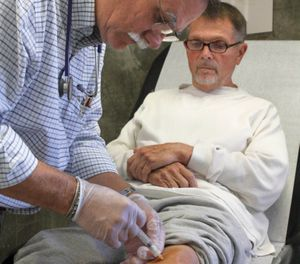In this Sept. 12, 2012, file photo Dr. David Mathis gives a cortisone shot to the knee of inmate Edwin Bergman at the California Medical Facility in Vacaville, Calif. (AP Photo/Rich Pedroncelli, File)