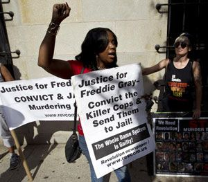 Demonstrators protest outside of the courthouse during the trial of Officer Caesar Goodson Jr. (AP Image)