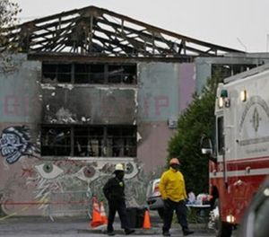 Fire officials walk past the remains of the Ghost Ship warehouse damaged from a deadly fire in Oakland, Calif. (AP Photo/Eric Risberg, File)