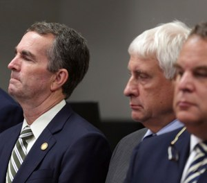 Virginia Gov. Ralph Northam, left, listens during a news conference in Virginia Beach, Va. Friday, May 31, 2019. (AP Photo/Vicki Cronis-Nohe)