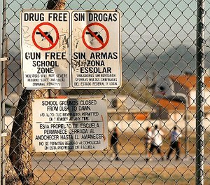 Drug and gun free school zone signs are shown as students play basketball at an elementary school Tuesday, Dec. 14, 2004, in Phoenix. (AP Photo/Matt York)