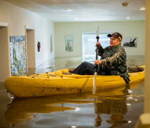 Lorin Doeleman uses a kayak to check her flooded home on Wednesday, Jan. 11, 2017, in Guerneville, Calif. (Santiago Mejia/San Francisco Chronicle via AP)