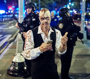 In this Oct. 31, 2017 file photo, a reveler gets his picture taken by a friend in front of heavily armed police during the Greenwich Village Halloween Parade in New York. The NYPD says thousands of uniformed and plainclothes officers will patrol the 2018 parade in Greenwich Village. They'll be joined by counterterrorism units, police dogs and helicopters. (AP Photo/Andres Kudacki, File)