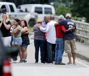 Family members react as a van is pulled out of the Greens Bayou with the bodies of six family members in Houston. (Elizabeth Conley/Houston Chronicle via AP)