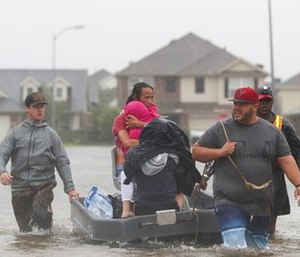Fran Cuong, second from left, shields his daughter from wind and rain as he and his family are rescued by Mason Broussard, left, Edrick Browne, right, and a third man, in rising floodwaters. (Jon Shapley/Houston Chronicle via AP)