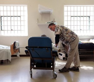 In this Sept. 12, 2012, file photo, Dr. David Mathis, visits with an inmate in the hospital unit at the California Medical Facility in Vacaville, Calif. (AP Photo/Rich Pedroncelli, File)