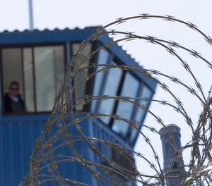In this Aug. 17, 2011, file photo, concertina wire and a guard tower are seen at Pelican Bay State Prison near Crescent City, Calif. (AP Photo/Rich Pedroncelli, File)