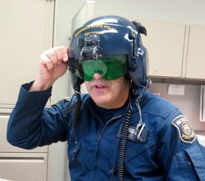 In a March 14, 2017 photo, Michigan State Police pilot Jerry King, shows a anti-laser shield in his office at a state police facility at Capital Region International Airport, in Lansing, Mich. (AP Photo/David Eggert)