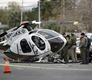 Las Vegas police officers stand by the wreckage of a Las Vegas police helicopter Wednesday, Dec. 31, 2014, in Las Vegas. (AP Image)