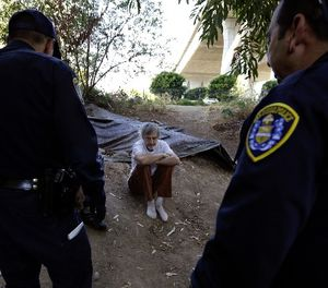 In this Sept. 28, 2017, photo, Stephen Schofield looks on as police officials encourage him to get a Hepatitis A vaccination near where is living along the San Diego River in San Diego. (AP Photo/Gregory Bull)