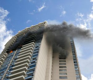 At least three people died and at least 12 were injured in a fire that broke out on the 26th floor of a Honolulu high-rise Friday, and hundreds fled from the giant apartment complex as smoke billowed from the upper floors, authorities said. (Photo/AP)