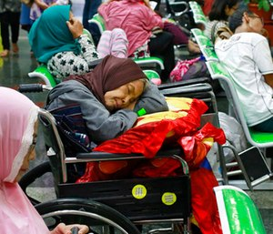 A patient takes a nap on her wheelchair as she waits with others at the registration desk at Dharmais Cancer Hospital in Jakarta, Indonesia. (AP Photo/Dita Alangkara)