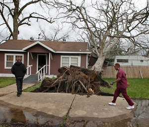 Cheryl Bradshaw, right, and her son Jerard walk past a toppled tree that separated her bathroom from her home Tuesday. (Steve Gonzales/Houston Chronicle via AP)