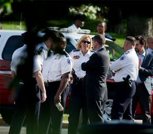District of Columbia Police Chief Cathy Lanier, center, talks to other officials at the scene of a house fire where four people were found dead after firefighters entered a home in an upscale Washington neighborhood. (AP Image)