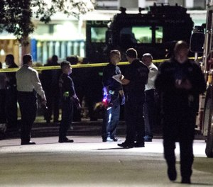 Houston police at the scene of a deadly shootout after a drug raid. The shooting left two civilians dead and five officers wounded (Photo/ Associated Press)