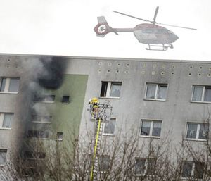 A helicopter flies over a high-rise building where a fire broke out, injuring more than a dozen people in Berlin. (Gregor Fischer/dpa via AP)