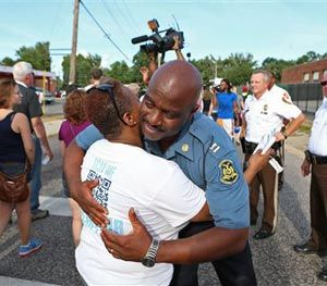 Capt. Ronald Johnson of the Missouri Highway Patrol hugs Angela Whitman, of Berkeley, Mo., on West Florissant Avenue in Ferguson, Mo., on Thursday, Aug. 14, 2014. (AP Image)