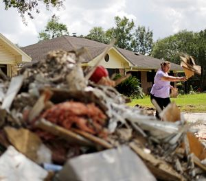 Maria Rocha places debris outside her home in a neighborhood that was flooded by Hurricane Harvey in Beaumont, Texas, Tuesday, Sept. 26, 2017. (AP Photo/David Goldman)