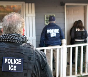 In this Feb. 9, 2017, photo provided U.S. Immigration and Customs Enforcement, ICE agents arrive at a home in Atlanta. (Bryan Cox/ICE via AP)