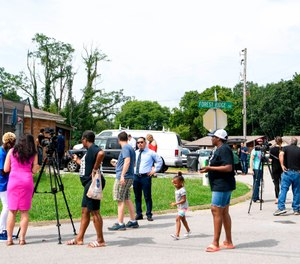 In this Monday, July 22, 2019 photo, media and concerned citizens gather outside a Nashville, Tenn., home, where an immigration agent gave up trying to arrest a Tennessee man. (Courtney Pedroza/The Tennessean via AP)