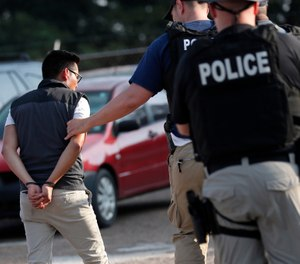 A man is taken into custody at a Koch Foods Inc. plant in Morton, Miss., on Wednesday, Aug. 7, 2019. (AP Photo/Rogelio V. Solis)