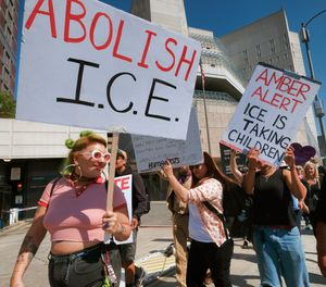 Protesters carry signs during a rally in front of the Immigration and Customs Enforcement facility in downtown Los Angeles on Monday, July 2, 2018. (AP Photo/Richard Vogel)