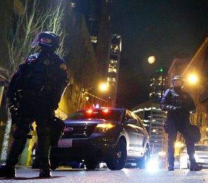 Law enforcement officers guard a side street during a protest march against President Donald Trump, Friday, Jan. 20, 2017, in Seattle. (AP Photo/Ted S. Warren)