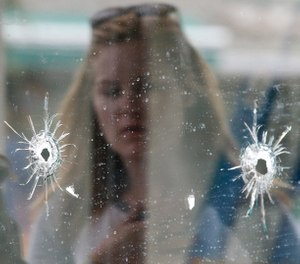 In this May 24, 2014 file photo, a woman looks at the bullet holes on the window of IV Deli Mark where a mass shooting took place near the University of California, Santa Barbara campus, in the Isla Vista beach community of Santa Barbara, Calif. (AP Photo/Jae C. Hong, file)