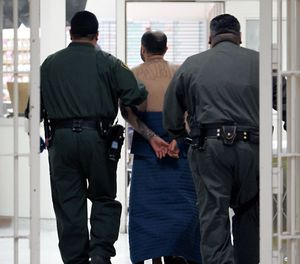 In this Jan. 14, 2009 file photo, an inmate, on suicide watch, is escorted by correctional officers at the California Substance Abuse Treatment Facility in Corcoran, Calif. (AP Photo/Rich Pedroncelli, File)