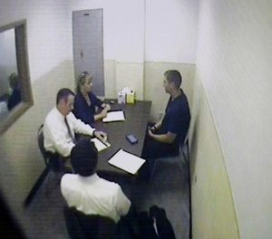 A photo of a video monitor showing Cincinnati Police Dept. Sgt. Shannon Heine and another Cincinnati police representative interviewing Ray Tensing, right. (Cara Owsley/The Cincinnati Enquirer via AP, Pool)