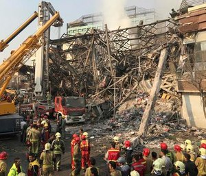 Iranian firefighters work at the scene of the collapsed Plasco building after being engulfed by a fire. (AP Photo/Ebrahim Noroozi)