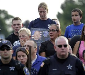 Mourners attend a vigil for Fox Lake Police Lt. Charles Joseph Gliniewicz on Wednesday, Sept. 2, 2015, in Fox Lake, Ill. (AP Image)