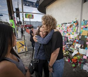 In this July 31, 2018 photo, MaryLinda Moss and Lynne Westafer, right, hug at a memorial outside the Trader Joe's in Silver Lake neighborhood of Los Angeles, where they were held hostage during an hours-long standoff on July 21. (Allen J. Schaben/Los Angeles Times via AP)