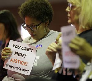 Alicia Street holds a sign as she sits in the audience during a meeting of the Ferguson City Council, Tuesday, March 15, 2016, in Ferguson, Mo. (AP Image)