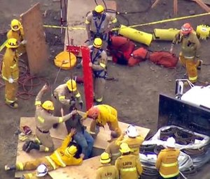 Firefighters used a fire truck's ladder like the boom of a crane to hoist the man up. (KTTV Fox11 News via AP)